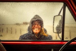 Germany, Schleswig-Holstein, St. Peter-Ording, beach, camping, Bulli, T3, window, laughing woman