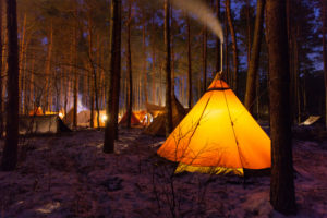 Tepee in the forest illuminated at night