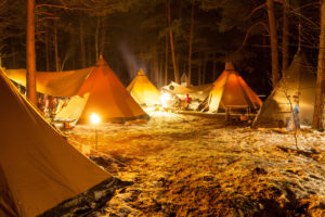 Tipi camp lit in the forest at night