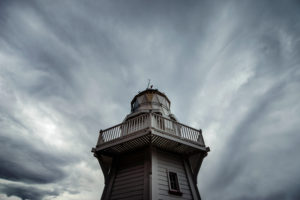 Wooden lighthouse in front of dramatic cloud front, Akaroa, Banks Peninsula, New Zealand