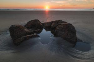 Broken stone ball of the Moeraki Boulders on the beach at sunrise, Koekohe Beach, New Zealand