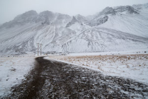 Snowy mountain landscape with gravel road and electricity pylon in the fog, Höfn, Austurland, Iceland