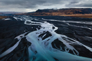 Aerial view of a branched river course with the Eyjafjallajökull massif and Seljalandsfoss in the background, Suderland, Iceland