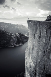 Person on the cliff of Preikestolen looks out over the Lysefjord, Rogaland, Norway