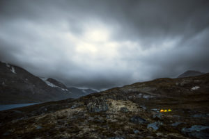 Three illuminated tents in a gloomy mountain landscape with a dramatic cloud mood, Jotunheimen, Norway