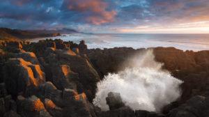 Fontäne aus einem Blowhole an den Pancake Rocks im Sonnenuntergang, Punakaiki, Paparoa-Nationalpark, Neuseeland