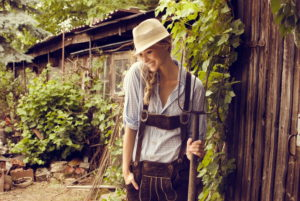 Woman, blond, leather trousers, checked blouse, hat, hayfork, woodsheds, stand, smile happy, half portrait,