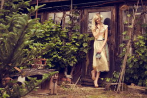 Blond woman, dirndl, woodshed, standing, cheerful, smiling, looking at camera,