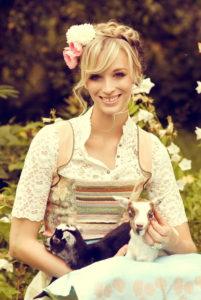 Blond woman, dirndl, meadow, sitting, happy, smiling, holding young goat in her arms,