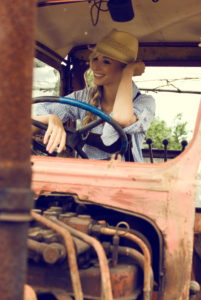 Blond woman, leather pants, checkered blouse, hat, tractor, old, sitting, happy, smiling,