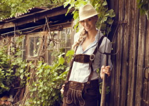 Blond woman, leather pants, checkered blouse, hat, pitchfork, wooden shed, standing, cheerful, smiling, looking at camera, half portrait,