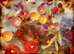 atmospheric table decoration with candles and blossoms in orange, yellow, red, brown and natural tones