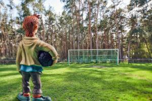Symbolbild Lockdown, Diorama, Miniatur, Fußballtor vor Waldstück, einsamer Junge mit Ball