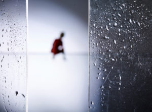 Symbolic image social distancing, silhouette of a lonely person, glass panes with droplets