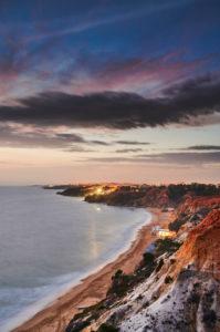 Europa, Portugal, Algarve, Litoral, Barlavento, Distrikt Faro, zwischen Vilamoura und Albufeira, Olhos de Agua, Sonnenuntergang an der Steilküste, Hochformat