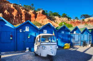 Europe, Portugal, Algarve, Litoral, Barlavento, Faro District, Praia dos Olhos de Agua, blue fishing huts in front of a red cliff with tuktuk