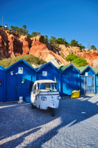 Europe, Portugal, Algarve, Litoral, Barlavento, district Faro, Praia dos Olhos de Agua, blue fishing huts in front of red-brown cliffs with tuktuk, portrait format