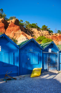 Europe, Portugal, Algarve, Litoral, Barlavento, District Faro, near Albufeira, Praia dos Olhos de Agua, blue fishing huts in front of red-brown cliffs, portrait format