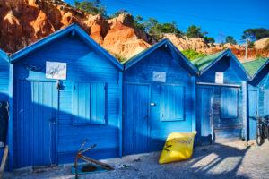Europe, Portugal, Algarve, Litoral, Barlavento, district of Faro, near Albufeira, Praia dos Olhos de Agua, blue fishing huts in front of red-brown cliffs