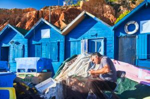 Europa, Portugal, Algarve, Litoral, Barlavento, Distrikt Faro, bei Albufeira, Praia dos Olhos de Agua, Fischer flickt Netze, blaue Fischerhütten vor rotbrauner Steilküste