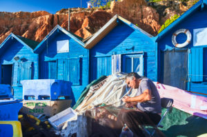 Europe, Portugal, Algarve, Litoral, Barlavento, Faro district, near Albufeira, Praia dos Olhos de Agua, fishermen mending nets, blue fishermen's huts off the red-brown cliffs