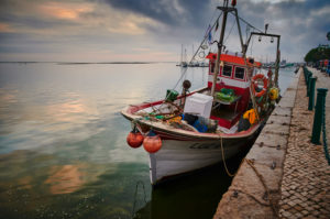 Europe, Portugal, Algarve, Litoral, Sotavento, Faro District, Olhao, Avenida 5 de Outubro, promenade at the market halls, fishing boat at sunset