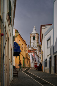 Europe, Portugal, Algarve, Litoral, Barlavento, Felsalgarve, Faro District, Lagos, street scene, alley with a view of the Igreja de Sao Sebastiao church, portrait format