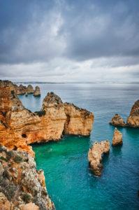 Europa, Portugal, Algarve, Litoral, Barlavento, Felsalgarve, Distrikt Faro, Lagos, Ponta da Piedade, Lagune mit Riff und Fernblick, Wolkenformationen, Hochformat