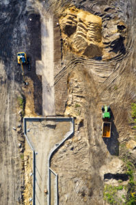 Infrastruktur, Erschließung eines Baugebiets, Erdbewegung, verschiedene Bodenarten werden sichtbar, Baufahrzeuge, Baulinien, Straßenführung, Hochformat