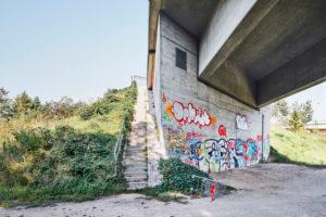 Architektur, Stadtraum, Öffentlicher Raum, Unter einer Brücke, Brückenpfeiler mit Graffiti, Brückenkopf mit Treppe, Friedrich-Ebert-Brücke in Lüneburg, Niedersachsen