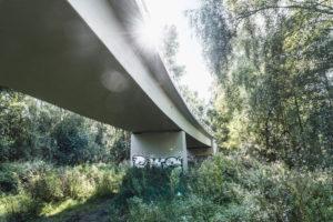 Architektur, Technik und Natur, Unter einer Brücke, Überbau im Gegenlicht, Sonnenfleck mit Lichtstrahlen, Vegetation am Ufer der Ilmenau, Niedersachsen,