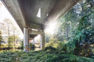 Architektur, Technik und Natur, Unter einer Brücke, Überbau im Gegenlicht, Sonnenfleck mit Lichtstrahlen, Betonbrücke über die Ilmenau und ein Bahngelände