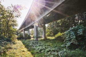 Architektur, Technik und Natur, Unter einer Brücke, Überbau im Gegenlicht, Sonnenfleck mit Lichtstrahlen, Betonbrücke über die Ilmenau und ein Bahngelände, Friedrich-Ebert-Brücke in Lüneburg, Niedersachsen