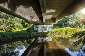 Architecture, technology and nature, under a bridge, bridgehead, superstructure with reflection in the water, concrete bridge over the Ilmenau, historic towpath between Lüneburg and Bardowick