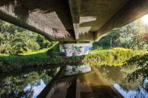 Architektur, Technik und Natur, Unter einer Brücke, Brückenkopf, Überbau mit Spiegelung im Wasser, Betonbrücke über die Ilmenau, Historischer Treidelweg zwischen Lüneburg und Bardowick