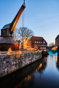 City view, Lüneburg, old town, water district, landmark, illuminated, old crane, Am Stintmarkt, Am Fischmarkt, Christmas, Christmas market, night shot, portrait format