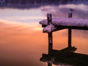 Spiegelung des Sonnenaufgangs im Pfäffikersee mit schneebedecktem Bootssteg