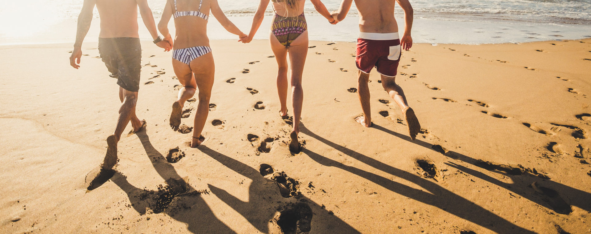 Back view people in summer holiday vacation running on the sand at the beach to the water sea all together in friendship holding hands - bikini group men and women have fun in the sunset with shadows