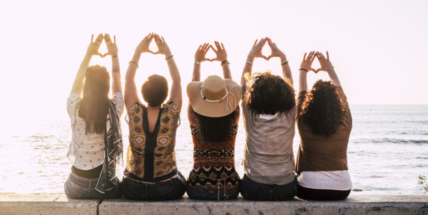 Group of young activist women viewed from rear doing feminism symbol and female power and respect with hands - sun and outdoor nature and sunset in background for group people