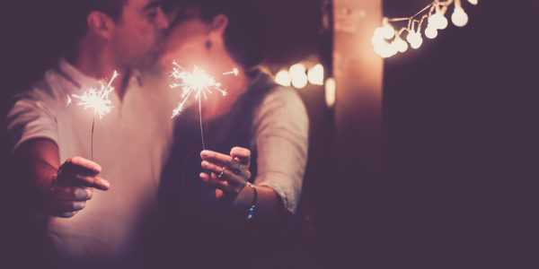 New year and romance couple of caucasian people man and woman kissing celebaring the nightlife party together - concept of couple in love with sparklers for celebrate event 2020