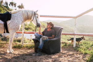 caucasian man enjoy his horse resting on a seats outdoor in the countryside. alternative lifestyle in contact with animals and nature. dog in the background
