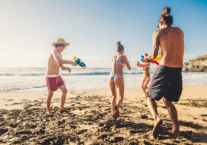 Group of people young caucasian men and women play with water gun at the beach during friends vacation together in outdoor in a sunny day of holiday - active youthful alternative millennial