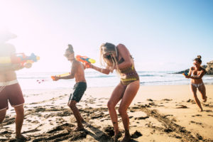 People having fun together in friendship at the beach playing with water guns in bikini under the hot summer sun - craziness and friends - bright image beautiful men and women with sea in background