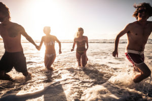 Group of beautiful millennial alternative young people have fun and enjoy the summer holiday vacation together in friendship running in the water of the ocean with sun in backlight