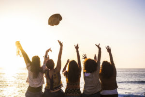 Summer and happiness for travel and freindship concept with group of happy girls viewed from rear enjoying and celebrating the sunset and the sea together launching hat and giving up