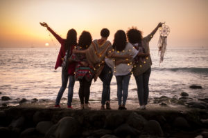 Dreaming image with group of females friends hug each other all together looking the sunset for friendship and love concept - Forever friends and dream lifestyle concept - people enjoying and feeling the life and the nature