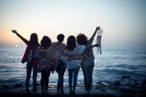 Romantic and dreamer concept image with five friends women hug each other viewed from back looking at the sunset holiding light - love freedom and wanderlust for group of people