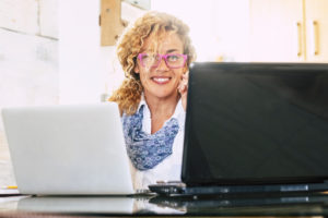 Beautiful blonde curly adul twoman wotk at the office with two laptop notebook at the same time - people at work concept - businesswoman using technology to work online at home
