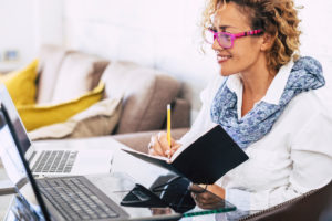 Young beautiful business woman smile and work with two different laptop - modern alternative office at home for independent people - secretary and business manager concept