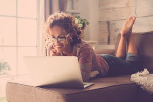 Woman smile and use an internet laptop connected to watch a movie or work easy at home in alternative office and lifestyle concept - freelance and free people with technology